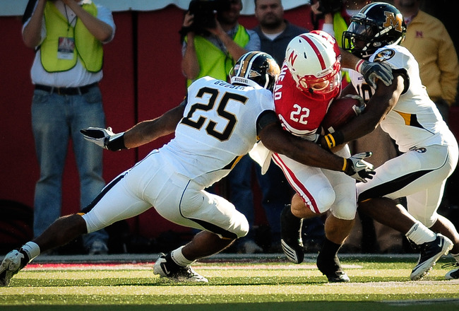 LINCOLN, NE - OCTOBER 30: Running back Rex Burkhead #22 of the Nebraska Cornhuskers fights for yardage between linebacker Zaviar Gooden #25 and defensive back Carl Gettis #19 of the Missouri Tigers during second half action of their game at Memorial Stadi