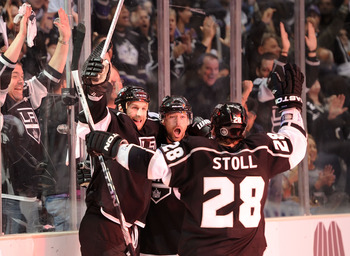 LOS ANGELES, CA - APRIL 21:  Justin Williams #14, Ryan Smyth #94 and Jarret Stoll #28 of the Los Angeles Kings celebrate after Williams goal against the San Jose Sharks in the second period of game four of the Western Conference Quarterfinals during the 2