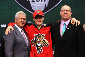 ST PAUL, MN - JUNE 24:  (L-R) General Manager Dale Tallon of the Florida Panthers, third overall pick Jonathan Huberdeau by the Florida Panthers and Director of Scouting Scott Luce of the Florida Panthers stand at the podium for a photo during day one of
