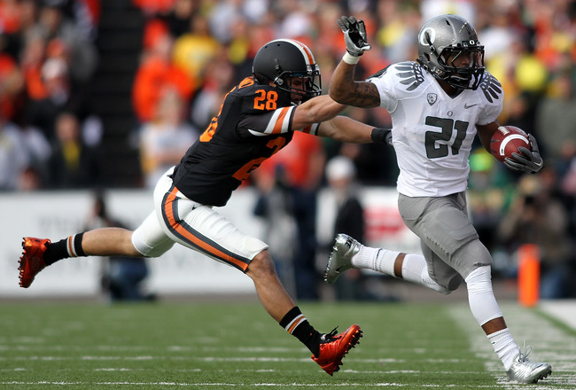 CORVALLIS, OR - DECEMBER 04:  LaMichael James #21 of the Oregon Ducks runs the ball against  Suaesi Tuimanei #28 of the Oregon State Beavers during the 114th Civil War on December 4, 2010 at the Reser Stadium in Corvallis, Oregon.  (Photo by Jonathan Ferr