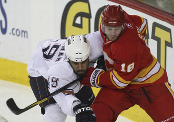 CALGARY, CANADA - APRIL 6: Matt Stajan #18 of the Calgary Flames uses his stick on Theo Peckham #49 of the Edmonton Oilers in first period NHL action on April 6, 2011 at the Scotiabank Saddledome in Calgary, Alberta, Canada. (Photo by Mike Ridewood/Getty