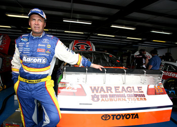 TALLADEGA, AL - APRIL 15:  Michael Waltrip, driver of the #15 Aaron's/Auburn National Champions Toyota, stands in the garage area during practice for the NASCAR Sprint Cup Series Aaron's 499 at Talladega Superspeedway on April 15, 2011 in Talladega, Alaba