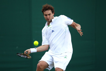 LONDON, ENGLAND - JUNE 22:  Ernests Gulbis of Latvia returns a shot during his first round match against Dmitry Tursunov of Russia on Day Three of the Wimbledon Lawn Tennis Championships at the All England Lawn Tennis and Croquet Club on June 22, 2011 in