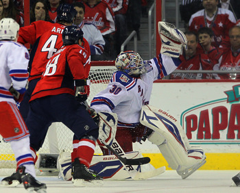 WASHINGTON, DC - APRIL 13: Henrik Lundqvist #30 of the New York Rangers comes up with a first period save on Mike Green #52 of the Washington Capitals (not shown) in Game One of the Eastern Conference Quarterfinals during the 2011 NHL Stanley Cup Playoffs