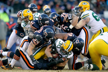 CHICAGO, IL - JANUARY 23:  John Kuhn #30 of the Green Bay Packers runs the ball as he is tackled by Chicago Bears defenders in the second half of the NFC Championship Game at Soldier Field on January 23, 2011 in Chicago, Illinois.  (Photo by Andy Lyons/Ge