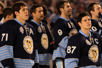 PITTSBURGH, PA - JANUARY 01:  Evgeni Malkin #71 and Sidney Crosby #87 of the Pittsburgh Penguins look on during the singing of the national anthem before playing against the Washington Capitals in the 2011 NHL Bridgestone Winter Classic at Heinz Field on