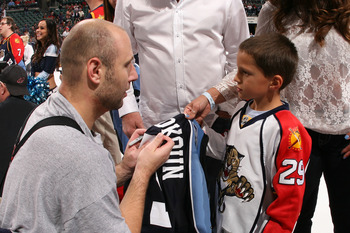 SUNRISE, FL - APRIL 9: Goaltender Tomas Vokoun #29 of the Florida Panthers signs his jersey for a young fan after it was won on auction after the game against the Washington Capitals on April 9, 2011 at the BankAtlantic Center in Sunrise, Florida. The Pan