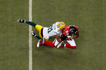 ATLANTA, GA - JANUARY 15:  Roddy White #84 of the Atlanta Falcons is tackled by Charles Woodson #21 of the Green Bay Packers during their 2011 NFC divisional playoff game at Georgia Dome on January 15, 2011 in Atlanta, Georgia.  (Photo by Kevin C. Cox/Get
