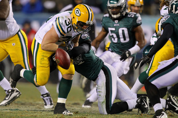 PHILADELPHIA, PA - JANUARY 09:  John Kuhn #30 of the Green Bay Packers loses the ball after getting tackled by Quintin Mikell #27 of the Philadelphia Eagles during the 2011 NFC wild card playoff game at Lincoln Financial Field on January 9, 2011 in Philad