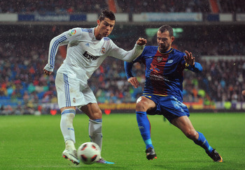 MADRID, SPAIN - FEBRUARY 19:  Cristiano Ronaldo  (L) of Real Madrid crosses the ball before being tackled by Juanfran of Levante during the  La Liga match between Real Madrid and Levante at Estadio Santiago Bernabeu on February 19, 2011 in Madrid, Spain.