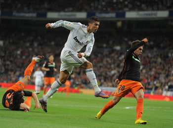 MADRID, SPAIN - APRIL 18:  Cristiano Ronaldo of Real Madrid shoots past Ever Banega (L) and Jordi Alba of Valencia during the La Liga match between Real Madrid and Valencia at Estadio Santiago Bernabeu on April 18, 2010 in Madrid, Spain.  (Photo by Denis