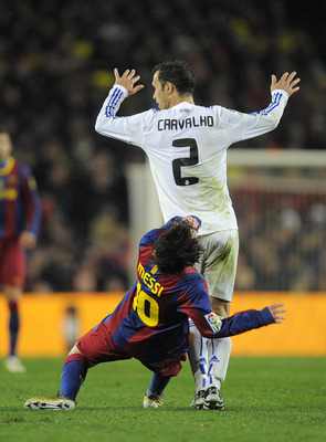 BARCELONA, SPAIN - NOVEMBER 29:  Lionel Messi of Barcelona (R) is hit by Ricardo Carvalho of Real Madrid during the La Liga match between Barcelona and Real Madrid at the Camp Nou Stadium on November 29, 2010 in Barcelona, Spain.  Barcelona won the match