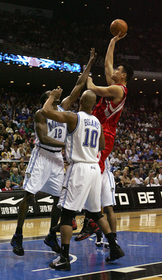 ORLANDO, FL - JANUARY 4: Yao Ming #11 of the Houston Rockets shoots over Dwight Howard #12 and Keith Bogans #10 of the Orlando Magic at Amway Arena January 4, 2008 in Orlando Florida. NOTE TO USER: User expressly acknowledges and agrees that, by downloadi