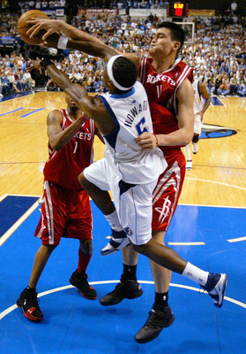 DALLAS - MAY 7:  Forward Josh Howard #5 of the Dallas Mavericks makes a pass around Yao Ming #11 and Tracy McGrady #1 of the Houston Rockets in Game seven of the Western Conference Quarterfinals during the 2005 NBA Playoffs at the American Airlines Center