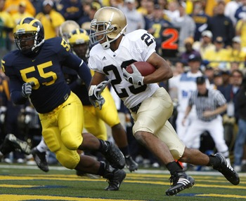 ANN ARBOR, MI - SEPTEMBER 15:  Golden Tate #23 of the Notre Dame Fighting Irish tries to turn the corner in front of Brandon Graham #55 of Michigan Wolverines at Michigan Stadium September 15, 2007 in Ann Arbor, Michigan. Michigan won the game 38-0.  (Pho