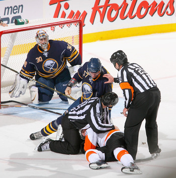 BUFFALO, NY - APRIL 20: Tyler Myers #57 of the Buffalo Sabres is pushed away from Danny Briere #48 of the Philadelphia Flyers by linesman Scott Cherrey #50 and Referee Marc Joannette #25 in Game Four of the Eastern Conference Quarterfinals during the 2011