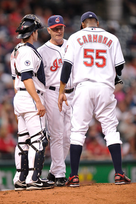 CLEVELAND, OH - JUNE 20:  Pitching Coach Tim Belcher #49 of the Cleveland Indians talks with pitcher Fausto Carmona #55 of the Cleveland Indians with catcher Lou Marson #6 of the Cleveland Indians during a game against the Colorado Rockies at Progressive