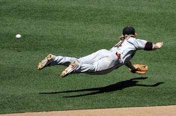 SAN DIEGO, CA - JULY 17: Mike Fontenot #14 of the San Francisco Giants dives for a single hit by Orlando Hudson #1 of the San Diego Padres during the fourth inning of a baseball game at Petco Park on July 17, 2011 in San Diego, California. (Photo by Denis