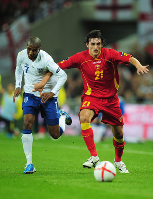 LONDON, ENGLAND - OCTOBER 12:  Ashley Young of England and Stefan Savic of Montenegro battle for the ball during the UEFA EURO 2012 Group G Qualifying match between England and Montenegro at Wembley Stadium on October 12, 2010 in London, England.  (Photo