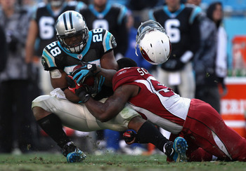CHARLOTTE, NC - DECEMBER 19:  O'Brien Schofield #50 of the Arizona Cardinals tackles Jonathan Stewart #28 of the Carolina Panthers as his helmet falls off during their game at Bank of America Stadium on December 19, 2010 in Charlotte, North Carolina.  (Ph
