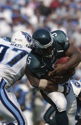 NASHVILLE, TN - SEPTEMBER 8:  Quarterback Donovan McNabb #5 of the Philadelphia Eagles runs past defensive end Carlos Hall #97 of the Tennessee Titans during the NFL game on September 8, 2002 at the Coliseum in Nashville, Tennessee. The Titans defeated th