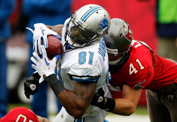TAMPA, FL - DECEMBER 19:  Receiver Calvin Johnson #81 of the Detroit Lions stretches for additional yardage as safety Corey Lynch #41 of the Tampa Bay Buccaneers tackles him during the game at Raymond James Stadium on December 19, 2010 in Tampa, Florida.