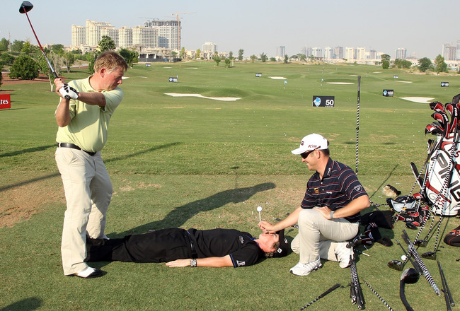 DUBAI, UNITED ARAB EMIRATES - NOVEMBER 24:  Rory McIlroy of Northern Ireland lies prone as Louis Oosthuizen of South Africa holds a very high tee on Rory's face as renowned trick shot artist David Edwards hits a full blown driver shot from the high tee on