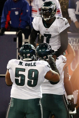 EAST RUTHERFORD, NJ - DECEMBER 13:  Michael Vick #7 of the Philadelphia Eagles celebrates after scoring a touchdown in the second quater with Todd Herremans #79 and Nick Cole #59 against the New York Giants at Giants Stadium on December 13, 2009 in East R