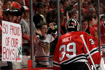 CHICAGO - MAY 29:  A fan holds up a sign reading 'So Proud of Our Boys' a Cristobal Huet #39 of the Chicago Blackhawks skates by before playing against the Philadelphia Flyers in Game One of the 2010 NHL Stanley Cup Final at the United Center on May 29, 2