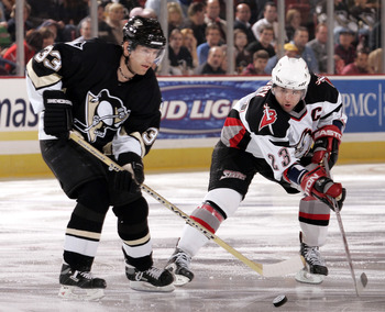 PITTSBURGH - NOVEMBER 29:  Ziggy Palffy #33 of the Pittsburgh Penguins tries to control the puck with defence coming from Chris Drury #23 of the Buffalo Sabres on November 29, 2005 at Mellon Arena in Pittsburgh, Pennsylvania.  (Photo by Gregory Shamus/Get