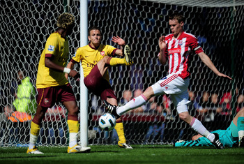 STOKE ON TRENT, ENGLAND - MAY 08:  Jack Wilshere of Arsenal clears the ball off his own goal line as Ryan Shawcross of Stoke closes in during the Barclays Premier League match between Stoke City and Arsenal at the Britannia Stadium on May 8, 2011 in Stoke