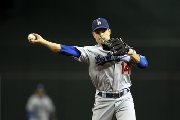 PHOENIX, AZ - JULY 15:  Infielder Jamey Carroll #14 of the Los Angeles Dodgers fields a ground ball out against the Arizona Diamondbacks during the Major League Baseball game at Chase Field on July 15, 2011 in Phoenix, Arizona. The Dodgers defeated the Di