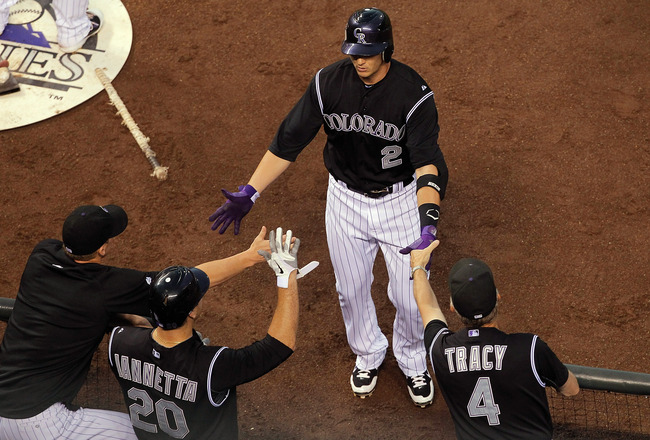 DENVER, CO - JULY 19:  Troy Tulowitzki #2 of the Colorado Rockies is congratulated by manager Jim Tracy #4, Chris Iannetta #20 and another teammate after hitting a three-run home run in the first inning against the Atlanta Braves at Coors Field on July 19