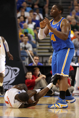 TAMPA, FL - MARCH 19:  Kenny Boynton #1 of the Florida Gators lies on the court in pain after he was injured as Joshua Smith #34 of the UCLA Bruins looks on during the third round of the 2011 NCAA men's basketball tournament at St. Pete Times Forum on Mar