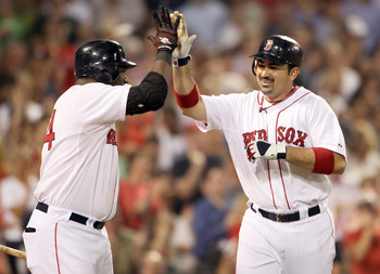 BOSTON, MA - JULY 07:  Adrian Gonzalez #28 of the Boston Red Sox is congratulated by teammate David Ortiz #34 after Gonzalez hit a solo home run in the fifth inning against the Baltimore Orioles on July 7, 2011 at Fenway Park in Boston, Massachusetts.  (P