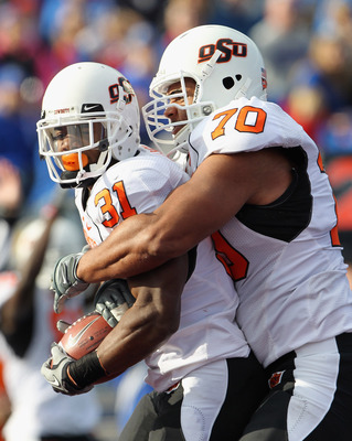 LAWRENCE, KS - NOVEMBER 20: Jeremy Smith #31 of the Oklahoma State Cowboys is congratulated by Jonathan Rush #70 after a touchdown during the game against the Kansas Jayhawks on November 20, 2010 at Memorial Stadium in Lawrence, Kansas.  (Photo by Jamie S