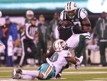 EAST RUTHERFORD, NJ - DECEMBER 12: Braylon Edwards #17 of the New York Jets is tackled by Chris  Clemons #30 of the Miami Dolphins at New Meadowlands Stadium on December 12, 2010 in East Rutherford, New Jersey.  (Photo by Nick Laham/Getty Images)