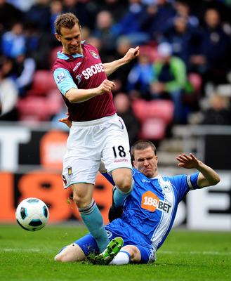 WIGAN, ENGLAND - MAY 15:  Jonathan Spector of West Ham United is tackled by Gary Caldwell of Wigan Athletic during the Barclays Premier League match between Wigan Athletic and West Ham United at the DW Stadium on May 15, 2011 in Wigan, England. (Photo by