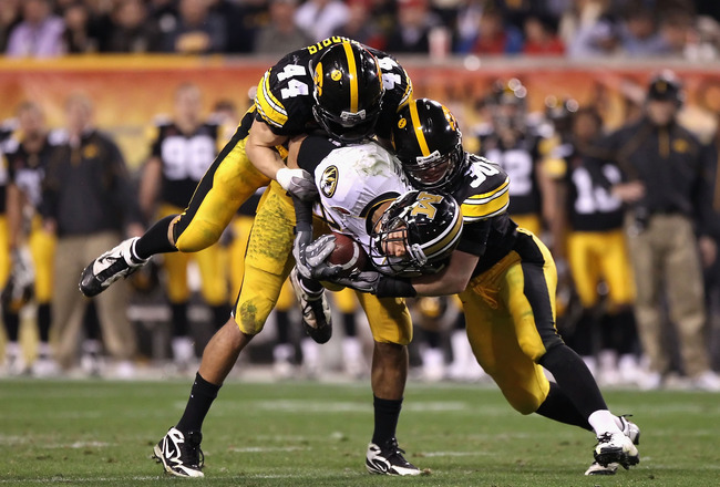 TEMPE, AZ - DECEMBER 28:  Wide receiver Michael Egnew #82 of the Missouri Tigers is tackled by James Morris #44 and Brett Greenwood #30 of the Iowa Hawkeyes after a 16 yard reception during the Insight Bowl at Sun Devil Stadium on December 28, 2010 in Tem