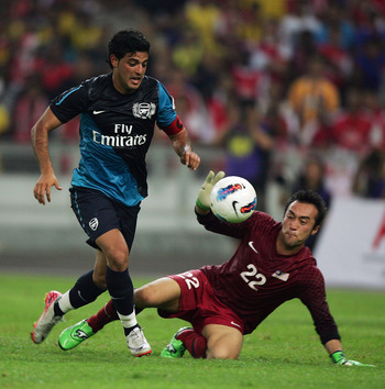 KUALA LUMPUR, MALAYSIA - JULY 13: Carlos Vela, goal keeper of Arsenal, competes with Mohd Nasril of Malaysia during the pre-season Asian Tour friendly match between Malaysia and Arsenal at Bukit Jalil National Stadium on July 13, 2011 in Kuala Lumpur, Mal