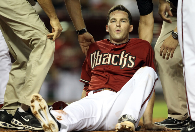 PHOENIX, AZ - JULY 20:  Stephen Drew #6 of the Arizona Diamondbacks reacts in pain after he was tagged out by catcher Jonathan Lucroy (not pictured) of the Milwaukee Brewers as he attempted to score during the fourth inning of the Major League Baseball ga