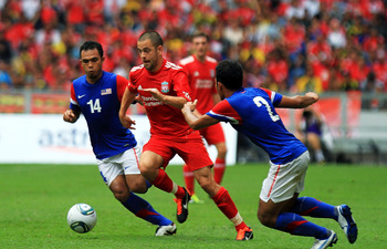 KUALA LUMPUR, MALAYSIA - JULY 16: Joe Cole of Liverpool evades tackle from Abdul Hadi Yahaya and Mahalli Jasuli of Malaysia during the pre-season friendly match between Malaysia and Liverpool at the Bukit Jalil National Stadium on July 16, 2011 in Kuala L