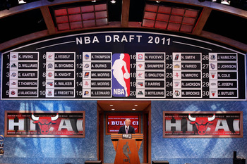 NEWARK, NJ - JUNE 23:  A general view of the names on the draft board after the completion of the first round as NBA Commissioner David Stern speaks at the podium during the 2011 NBA Draft at the Prudential Center on June 23, 2011 in Newark, New Jersey.
