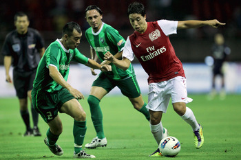 HANGZHOU, CHINA - JULY 16:  Samir Nasri (R) of Arsenal battles for the ball with Shaokun Wu of Hangzhou Greentown during the pre-season friendly match between Hangzhou Greentown and Arsenal at Yiwu Meihu Stadium on July 16, 2011 in Hangzhou, China.  (Phot