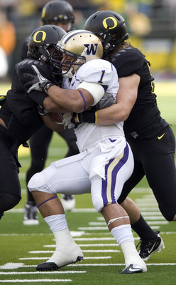 EUGENE, OR - NOVEMBER 6: Linebackers Spencer Paysinger #35 and Casey Matthews #55 of the Oregon Ducks gang up to tackle running back Chris Polk #1 of the Washington Huskies in the first quarter of the game at Autzen Stadium on November 6, 2010 in Eugene,