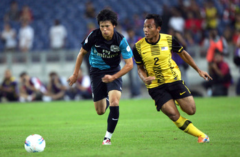 KUALA LUMPUR, MALAYSIA - JULY 13: Ryo Miyaichi of Arsenal is chased by M. Jasuli of Malaysia during the pre-season Asian Tour friendly match between Malaysia and Arsenal at Bukit Jalil National Stadium on July 13, 2011 in Kuala Lumpur, Malaysia.  (Photo b