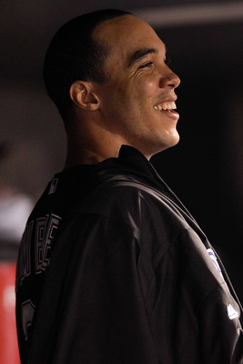 DENVER, CO - JULY 19:  Starting pitcher Ubaldo Jimenez #38 of the Colorado Rockies laughs in the dougout after being taken out after 6 2/3 innings as the Rockies lead the Atlanta Braves 10-2 at Coors Field on July 19, 2011 in Denver, Colorado.  (Photo by