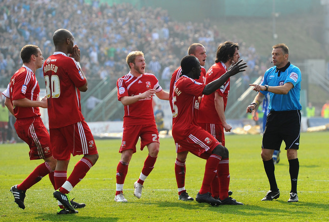 BRIGHTON, ENGLAND - MARCH 26:  Referee Mark Halsey is surrounded by furious Swindon players after awarding Brighton their second penalty during the npower League One match between Brighton & Hove Albion and Swindon Town at the Withdean Stadium on March 26