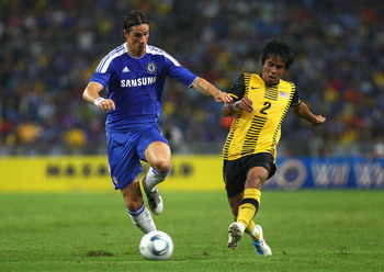 KUALA LUMPUR, MALAYSIA - JULY 21:  Fernando Torres of Chelsea competes for the ball against Mohd Daudsu Jamaluddin of Malaysia during the pre-season friendly match between Malaysia and Chelsea at Bukit Jalil National Stadium on July 21, 2011 in Kuala Lump