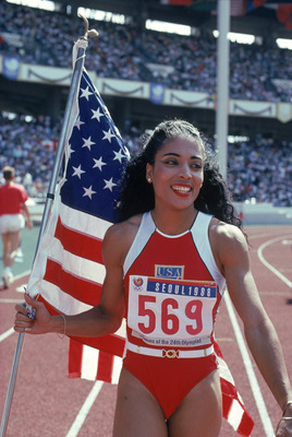 SEOUL, SOUTH KOREA - SEPTEMBER 28:  Florence Griffith Joyner of the USA walks with the American Flag as she celebrates setting a new Olympic record to win the gold medal in the Women's 100 meters dash final during the 1988 Summer Olympic Games on Septembe